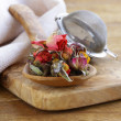 Herbal tea from the dried flower buds of roses in a wooden spoon — Stock Photo #34200751