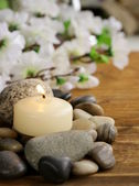 Still life a lit candle and stones on wooden background — Stockfoto