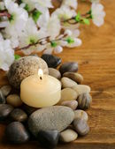Still life a lit candle and stones on wooden background — 图库照片