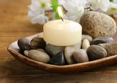 Still life a lit candle and stones on wooden background — Zdjęcie stockowe
