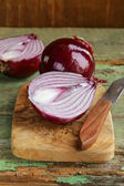 Sweet red onions on a wooden chopping board — Stok fotoğraf
