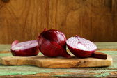 Sweet red onions on a wooden chopping board — Stock Photo