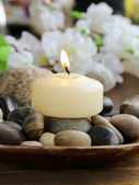 Still life a lit candle and stones on wooden background — Stock Photo