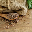Stock Photo: Dry buckwheat groats on wooden table
