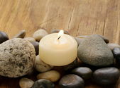 Still life a lit candle and stones on wooden background — Stock fotografie