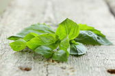 Fresh green basil leaves on a wooden background — Stock Photo