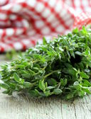Bunch of fresh green thyme on a wooden table — Stock Photo