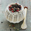 Colorful peppercorn in wicker bowl on wooden table — Stock Photo #36946295