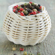 Colorful peppercorn in wicker bowl on wooden table — Stock Photo #36946307