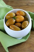 Green marinated olives in a white bowl — Stock Photo