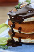 Homemade pancakes with chocolate syrup and thyme — Stock Photo