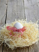 Easter eggs in nest on a wooden background — Stock Photo