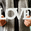 Man holding the wooden word love soft focus on the letters — Stock Photo #37991233