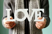 Man holding the wooden word love soft focus on the letters — Stockfoto
