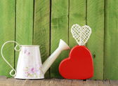 Still life for Valentine's Day - ceramic heart and watering can on a wooden background — Stock Photo