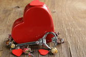 Still life red heart with key on the old wooden background — Stock Photo
