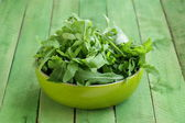 Bowl of green salad with arugula on wooden table — Stock Photo