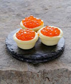 Gourmet tartlets with red caviar on a stone plate — Stock Photo