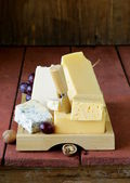 Cheese assortment served on a wooden board with grapes — Stock Photo
