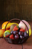 Still life wicker basket with fruit on a wooden table — Stock Photo