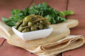 Pickled capers in bowl on a wooden table — Stock Photo