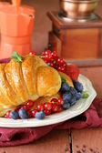 Fresh croissant with berries for breakfast on vintage plate — Stock Photo
