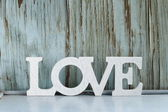 Word love made of white wooden letters on vintage background — Stock Photo