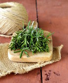 Fresh green rosemary on a wooden chopping board — Stock Photo