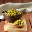 Canned green peas in a wooden spoon — Photo