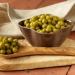 Canned green peas in a wooden spoon — Zdjęcie stockowe