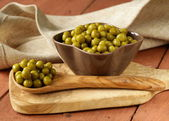 Canned green peas in a wooden spoon — Stock Photo