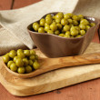 Canned green peas in a wooden spoon — Stockfoto #39650745