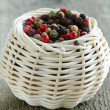 Colorful peppercorn in wicker bowl on wooden table — Stock Photo