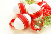 Festive eggs decorated with red ribbon - symbol of Easter holiday — Stock Photo