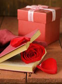 Romantic still life book and red rose on wooden background — Foto Stock
