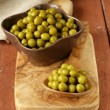Canned green peas in a wooden spoon — Foto de Stock