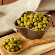 Canned green peas in a wooden spoon — Stok fotoğraf