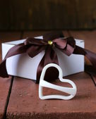 White gift box with ribbon bow on a wooden background — Photo