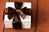White gift box with ribbon bow on a wooden background — Stok fotoğraf