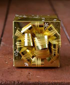 Gold festive gift box with bow on top — Zdjęcie stockowe