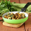 Foto Stock: Fried champignon mushrooms with thyme in pan