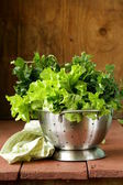 Green lettuce and parsley in a metal colander — Stock Photo