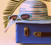 Old fashioned blue suitcase for travel and beach hat — Stock Photo