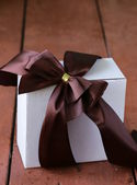 White gift box with ribbon bow on a wooden background — ストック写真
