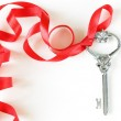 Vintage key with a festive beautiful red ribbon — Stock Photo