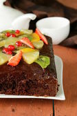 Chocolate brownie cake decorated with different fruits — Stock Photo
