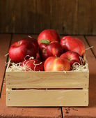 Fresh ripe organic red apples in a wooden box — Stock Photo