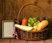 Picnic basket - wine, fruit, cheese and sausage — Stock Photo