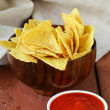 Corn tortilla chips in a bowl with tomato sauce — Stock Photo