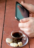 Cup of coffee for a businessman with digital tablet in the background — Foto de Stock